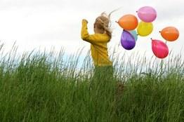 Kind mit Luftballons auf einer Wiese